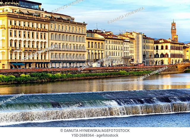 Florence at dusk, chic hotels along Arno river, Palazzo Vecchio tower on right, Tuscany, Italy