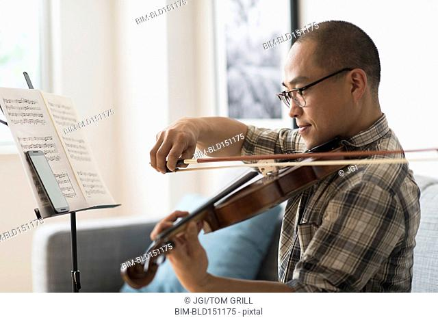 Korean musician playing violin in living room