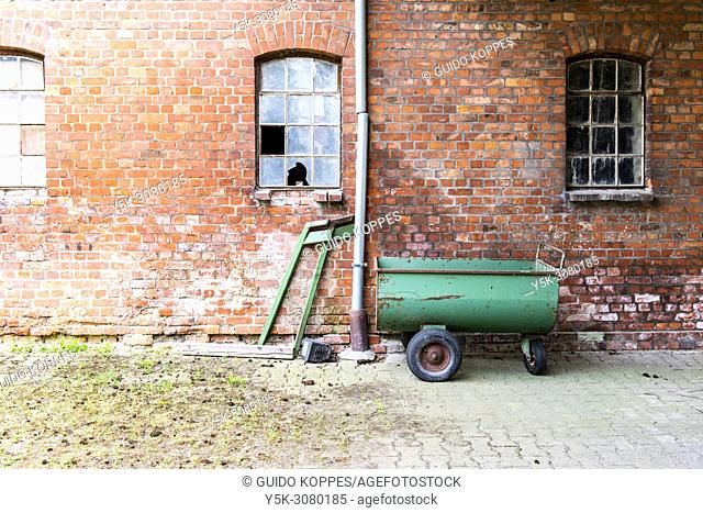 Niedersachsen, Germany. Exterior of a farmhouse stable with a small fluid or septic tank parked outside