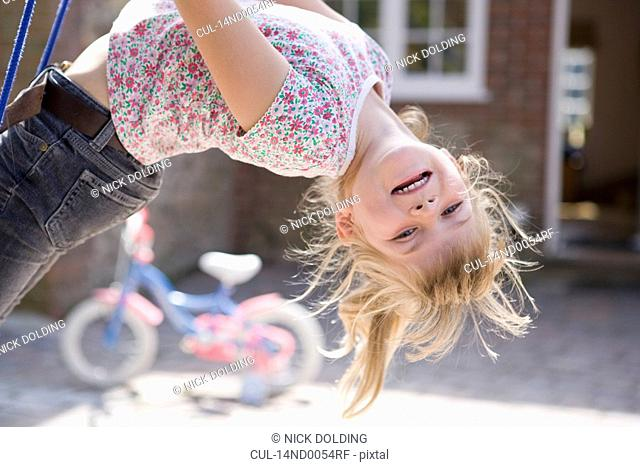 Young girl upside down on swing