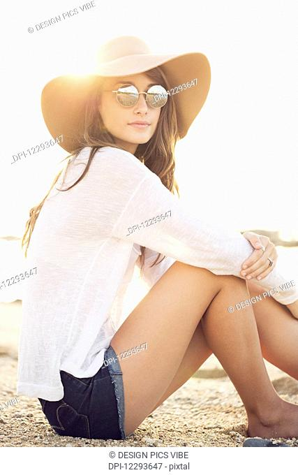Fashion portrait of beautiful young woman wearing sunglasses and hat on the beach, bright warm sunny backlit color tone