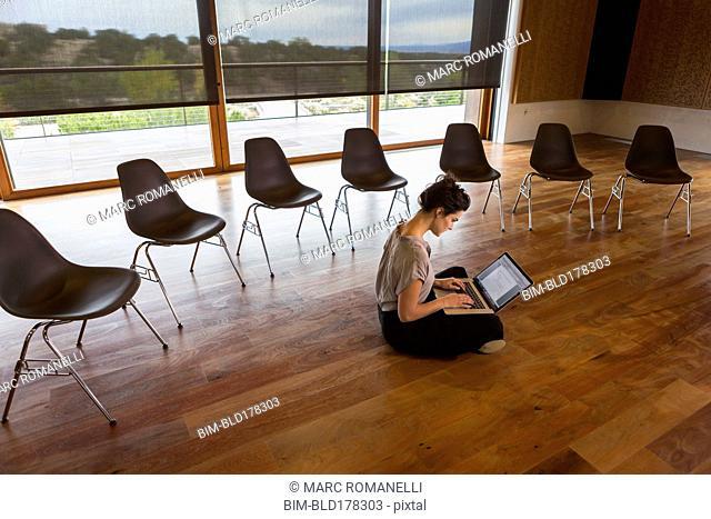 Mixed race businesswoman using laptop on floor of meeting room