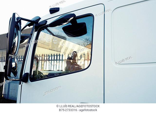 Driver relaxing inside van. London, England