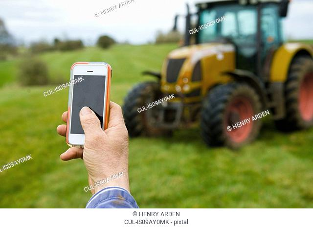Hand of farmer photographing tractor on smartphone