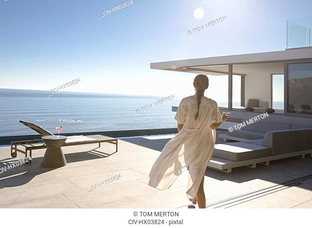 Woman walking on sunny modern, luxury home showcase exterior patio with ocean view