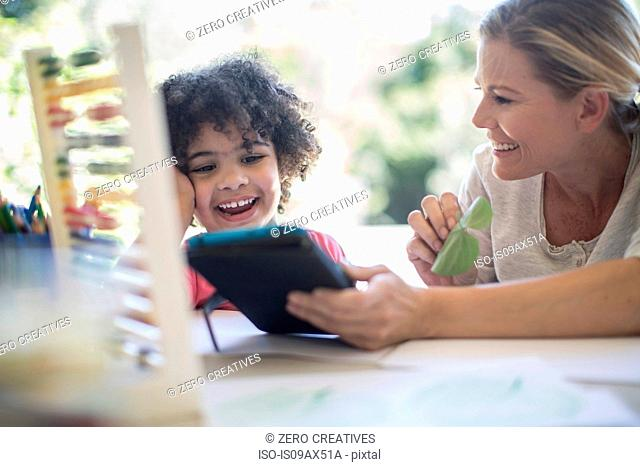 Mother and son sitting at table, playing together, using digital tablet
