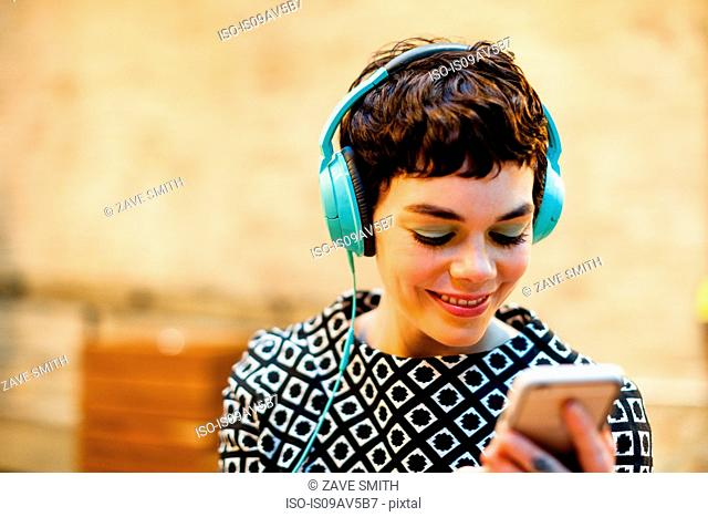 Mid adult woman, wearing headphones, looking at smartphone, smiling