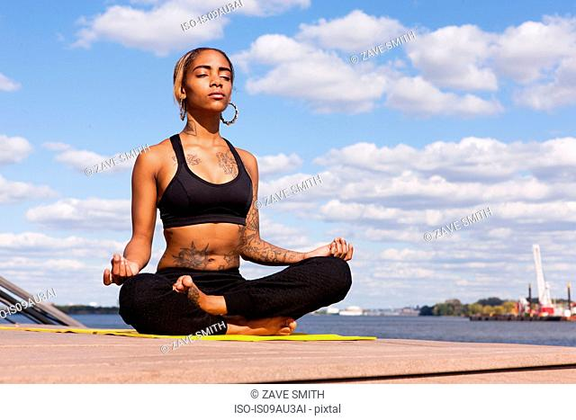 Young woman sitting cross legged by water in yoga position, eyes closed, Philadelphia, Pennsylvania, USA