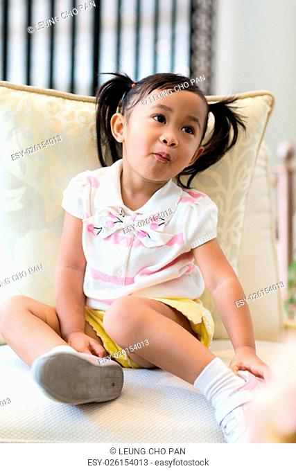 Cuty little girl with candy in mouth and sitting on sofa