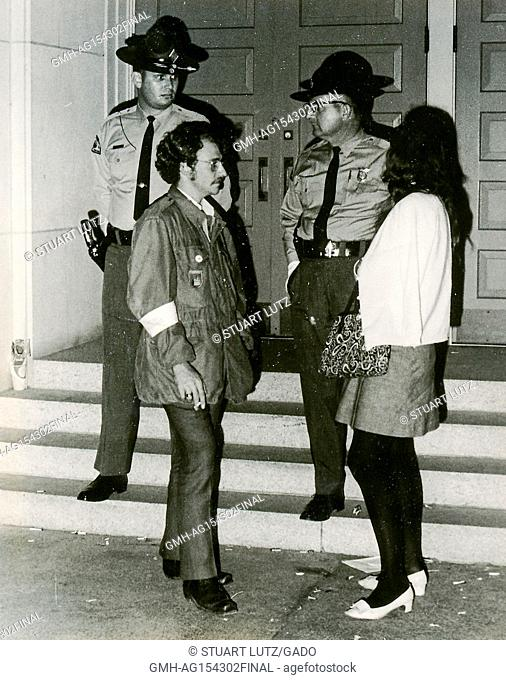 Sheriff's deputies, one with a handgun in a holster, stand on the steps of a building and appear tense while speaking with two people during an anti Vietnam War...