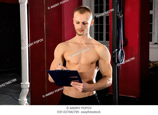 Portrait Of An Athlete Man Writing A Workout Plan On Clipboard In The Gym