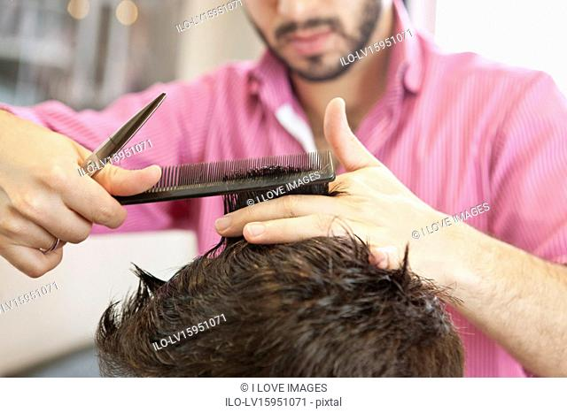 A male hairdresser cutting his male clients hair with scissors, close up