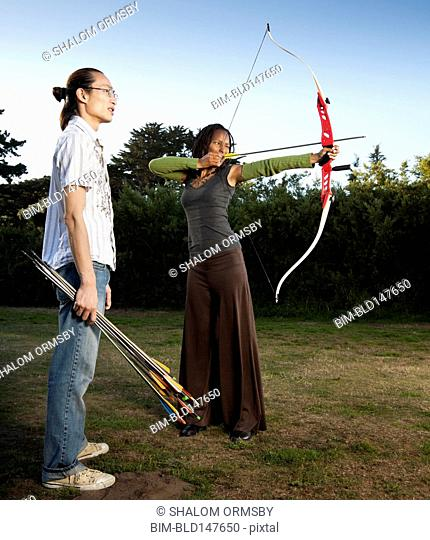 Man watching archer aiming bow and arrow