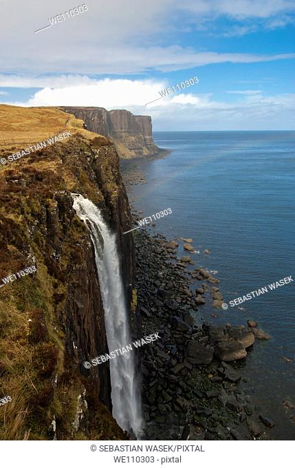 Waterfall flowing over the cliffs of the coast of Isle of Skye, Kilt Rock is in the distance, Scotland, UK, Europe