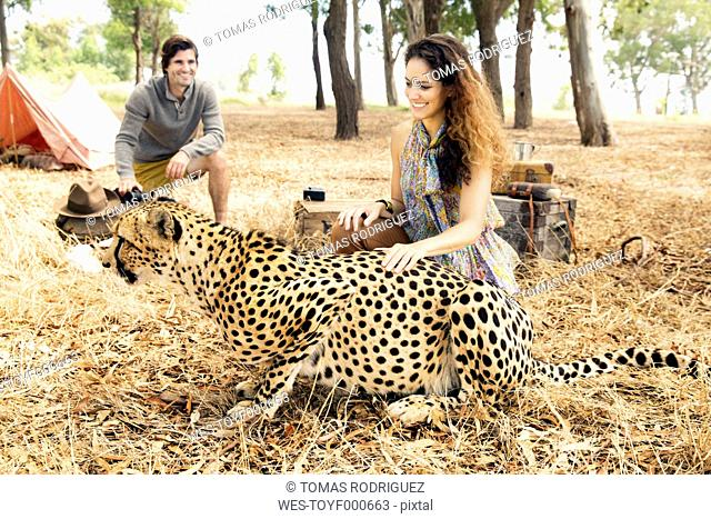 South Africa, woman petting tame cheetah on meadow with man in background
