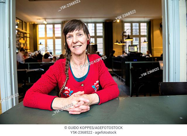 Tilburg, Netherlands. Portrait of a 61 year old colorful dressed and fashionable woman preparing for lunch in a daytime cafe-restaurant