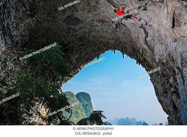 Low angle view of rock climber on Moon Hill, Yangshuo, Guangxi Zhuang, China