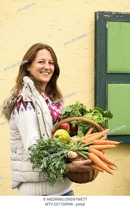 Portrait of a mid adult woman holding basket full of vegetables and smiling, Bavaria, Germany