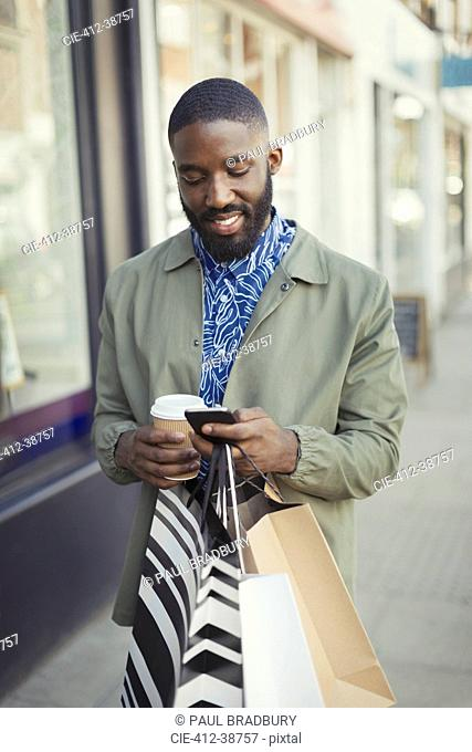 Smiling young man with coffee and shopping bags texting with cell phone on urban sidewalk