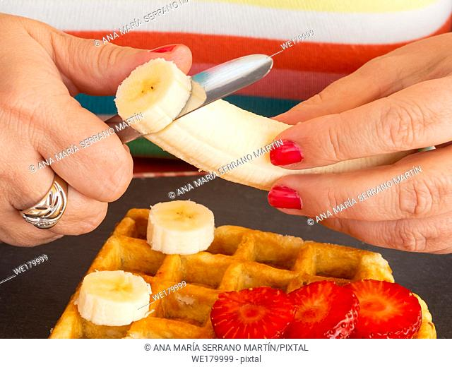 A woman with red fingernails cutting strawberry and banana and placing it on a Belgian waffle