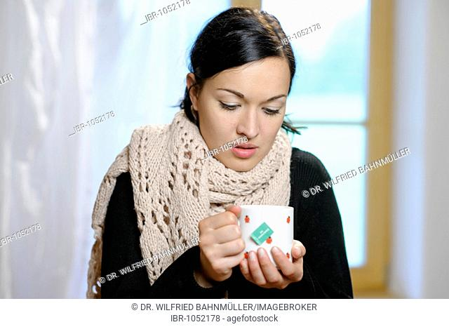 Young woman with a cup of tea, getting a cold, flu, fever, feeling cold, ill