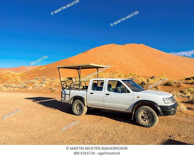 Terrain vehicle in front of a sand dune of the Namib Desert, Hardap Region, Namibia