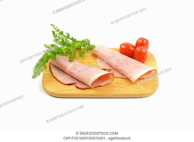 two ham slices with dill an cherry tomatoes on wooden cutting board