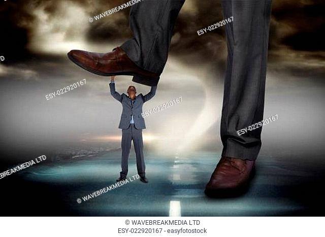 Composite image of businessman stepping on tiny businessman against stormy sky with tornado over road