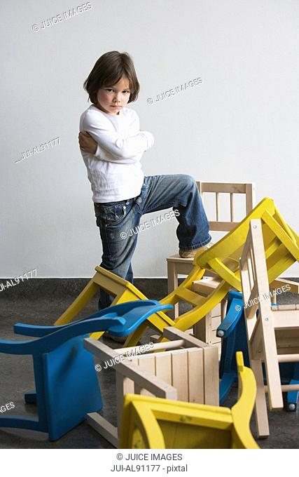 Preschool boy standing on pile of chairs