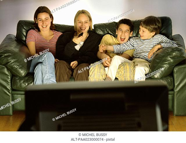 Three young people and one child sitting on green couch together, laughing, blurred rear view of tv in foreground