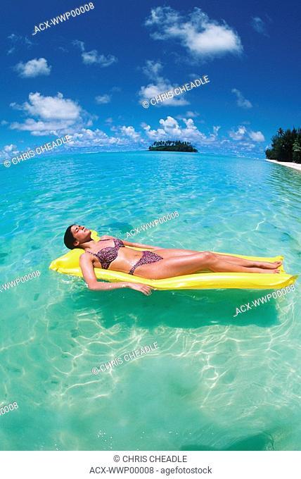 Cook Islands, South Pacific, Raratonga, Muri Lagoon, young woman on yellow float