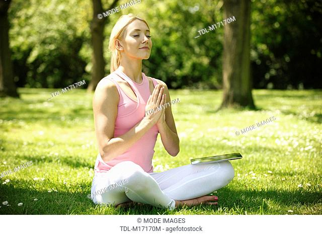 A young woman practicing yoga outside, hands in prayer position