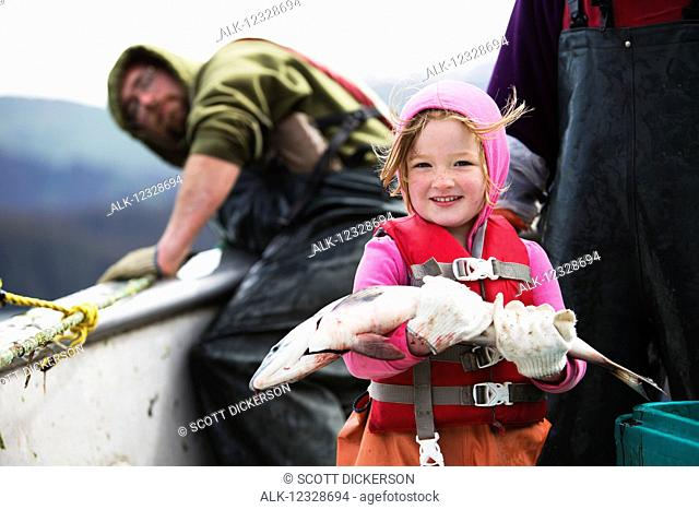 Young girl holding a fresh caught salmon while in her family's set-net skiff with her mother, Seldovia, South-central Alaska; Alaska, United States of America