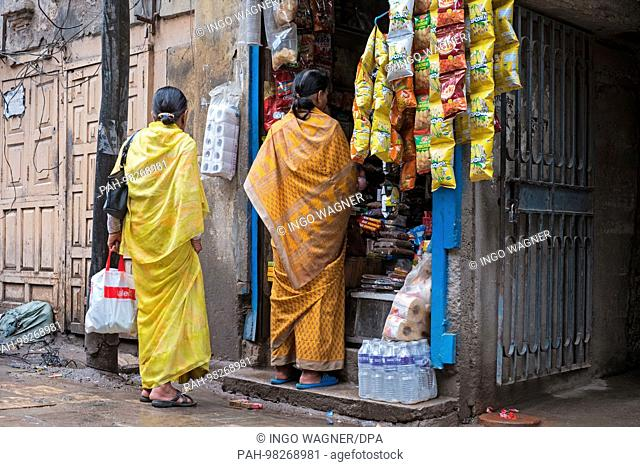 Two colored dressed women stand in front of a small grocery store in the Nepali capital Kathmandu.   usage worldwide. - Kathmandu/Nepal