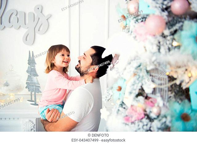 Little daughter and father near Christmas tree. Happy New Year