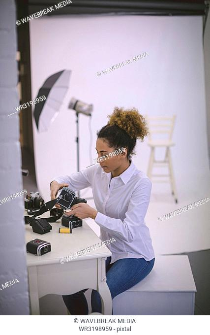 Female photographer removing reel from digital camera