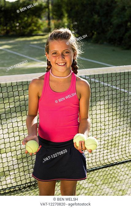 A teenage girl on a tennis court with tennis balls; Tarifa, Cadiz, Andalusia, Spain