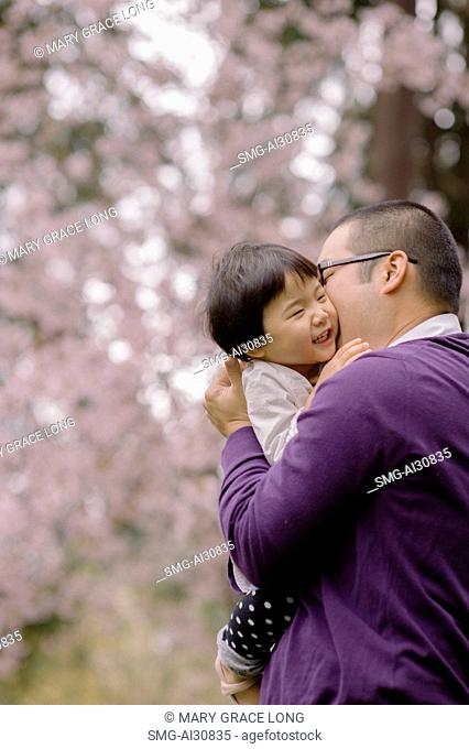 USA, Father kissing daughter (2-3) in park