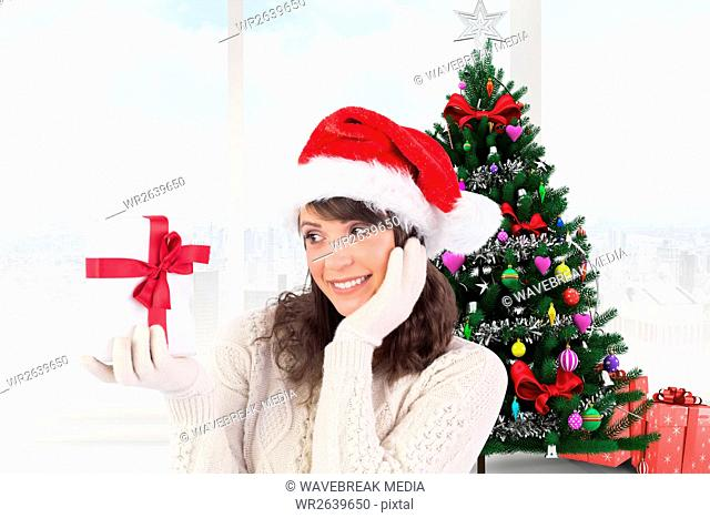 Excited woman in santa hat looking at gift box