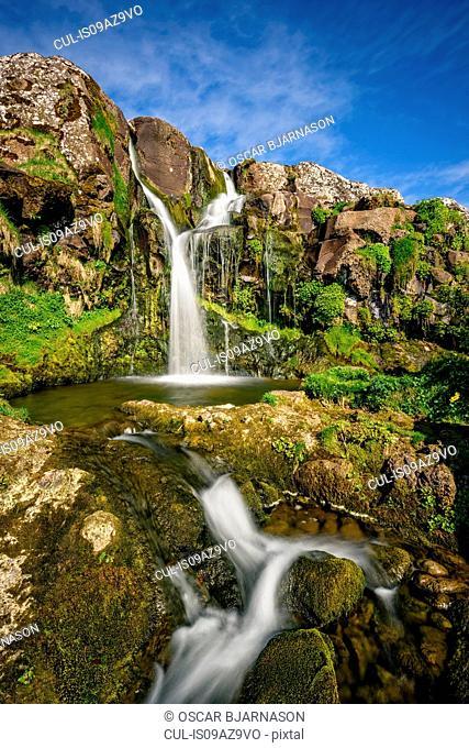 Waterfall on lush green cliff, Torshavn, Faroe Islands
