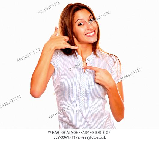 Portrait of a smiling young woman pointing and saying at you call me against white background