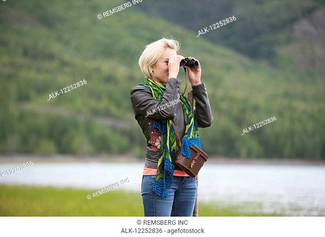 Woman using binoculars at Eklutna Lake, Chugach Mountains, Chugach State Park, Southcentral Alaska