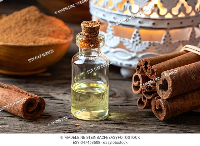 A bottle of essential oil with cinnamon sticks and powder on a table