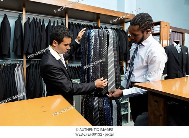 Tailor showing ties to client in tailor shop
