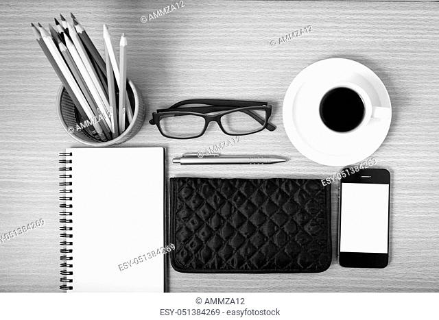 office desk: coffee with phone, notepad, eyeglasses, wallet, color pencil box on wood background black and white color