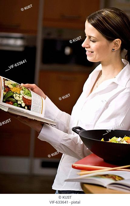 junge Frau sucht Wokgericht in einem Kochbuch - Nieder÷sterreich, Ísterreich, 14/02/2008