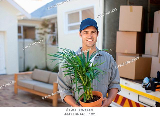 Smiling man carrying Flowerpot moving van