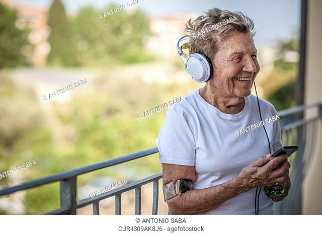 A very senior woman listening to music on headphones on apartment balcony