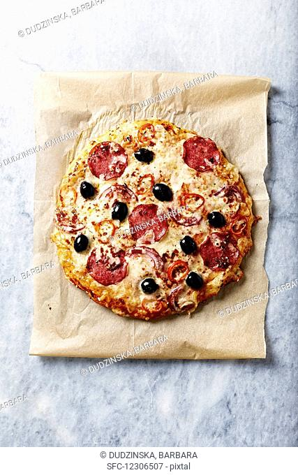 Rustic pizza with spicy salami, cheese and red chili peppers