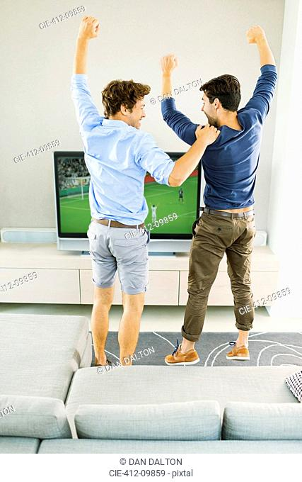 Men cheering and watching soccer game